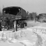 Грузовики ЗИЛ буксируют артиллерийские орудия по снегу, вид сзади, сбоку.